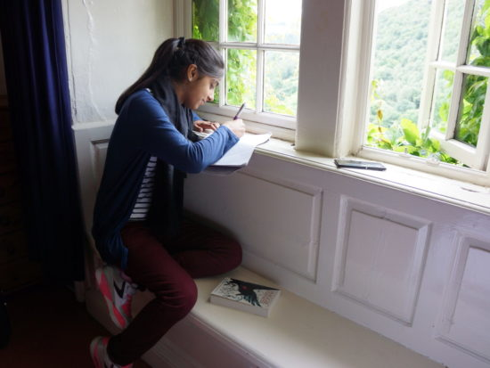 Girl writing at Arvon